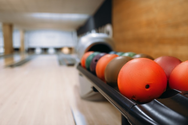 Color bowling balls in feeder, lane with pins, nobody. bowl game concept