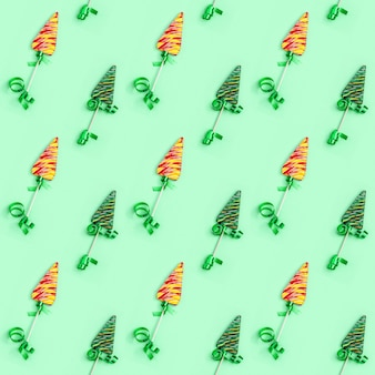Color candy creative seamless pattern for new year or christmas. lollipops shaped like christmas tree on green background.