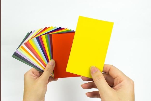 手にカラーカードペイントサンプル。手で修理するための塗料のパレット。