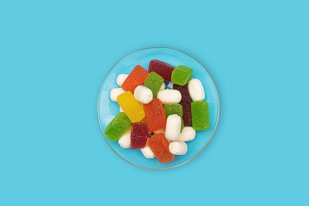 Цветные жевательные конфеты на синем фоне