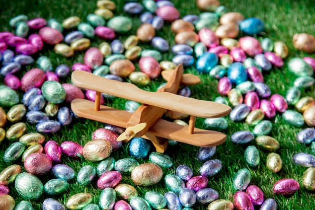 Color chocolate easter eggs and wooden airplane