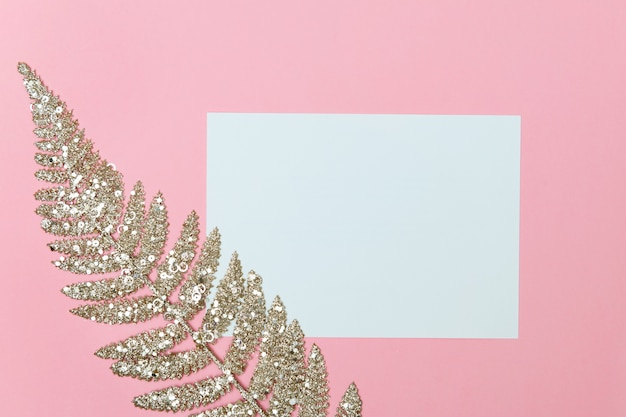 Color christmas background with golden glitters covered fern branch and empty blank for text flat lay copy space