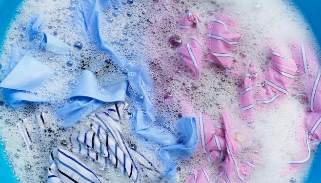 Цветная одежда впитывается порошком моющего средства при растворении воды. концепция прачечной