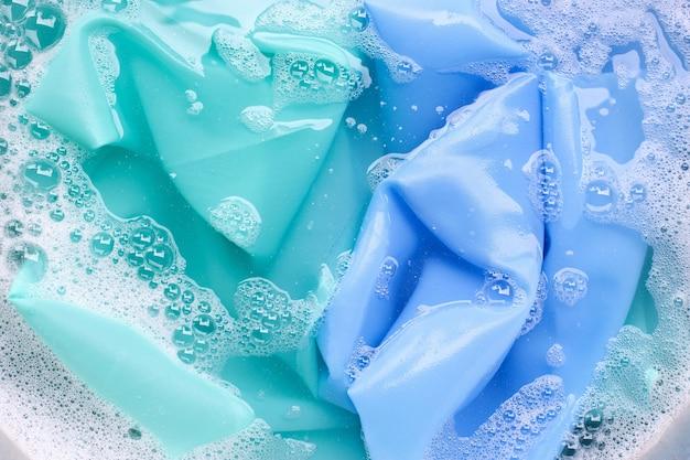 Цветную одежду замачивают в растворе воды в порошке. концепция прачечной
