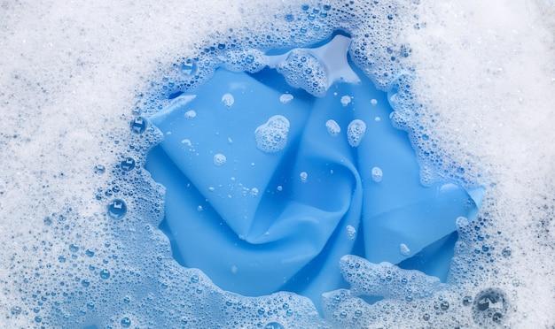 Цветная одежда замачивается в стиральном порошке, растворяющем воду