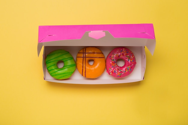 Color donuts in box on yellow background. free space. copy space.