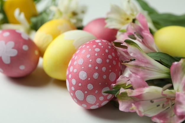 색상 부활절 달걀과 흰색 바탕에 alstroemeria 꽃을 닫습니다.