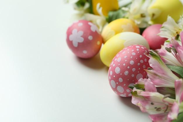 부활절 달걀과 흰색 바탕에 alstroemeria 꽃 색상
