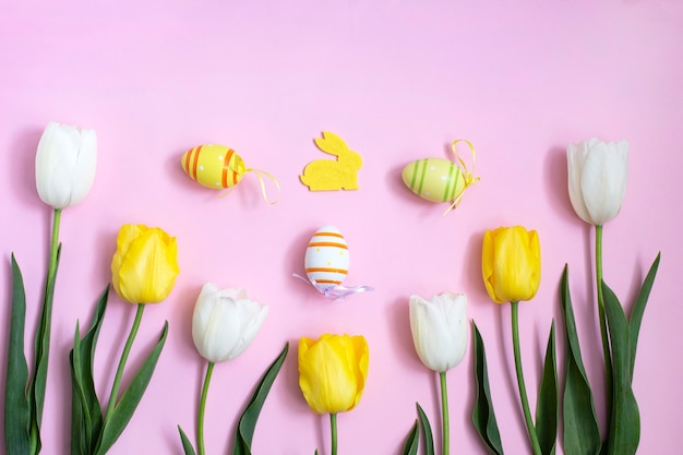 Color easter eggs and bunny with white, yellow tulips