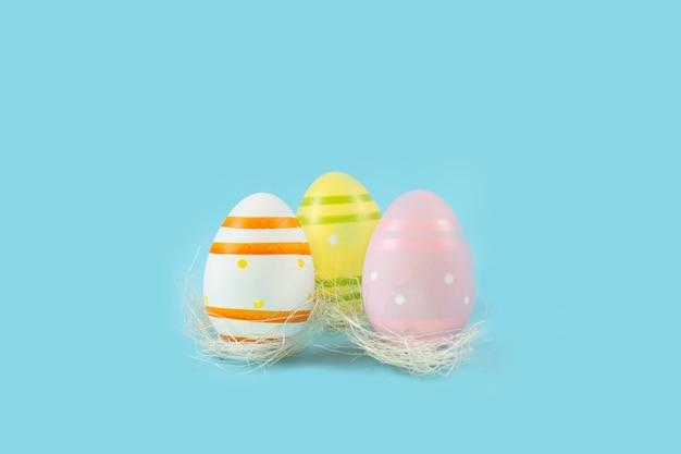 Цветные пасхальные яйца в белом гнезде на синем столе