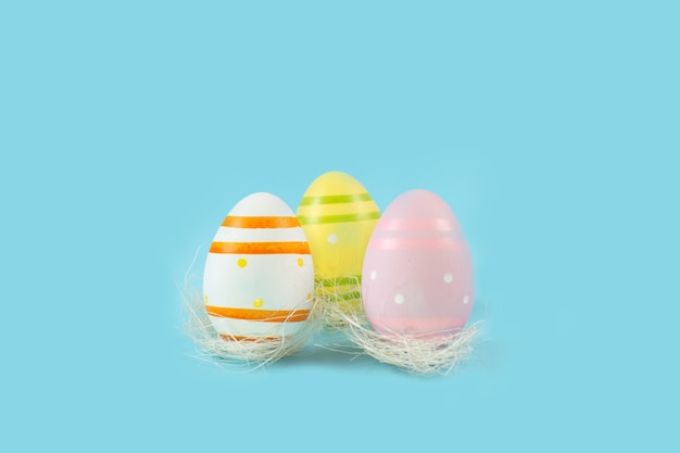 Color easter eggs in white nest on a blue desk