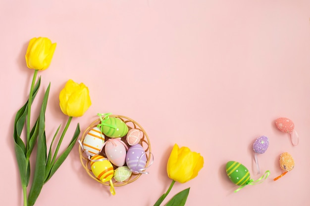 Color easter eggs and white yellow tulips on a pink background.