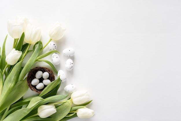 Цветное яйцо пасха и белый букет цветов тюльпанов на белом фоне с копией пространства.