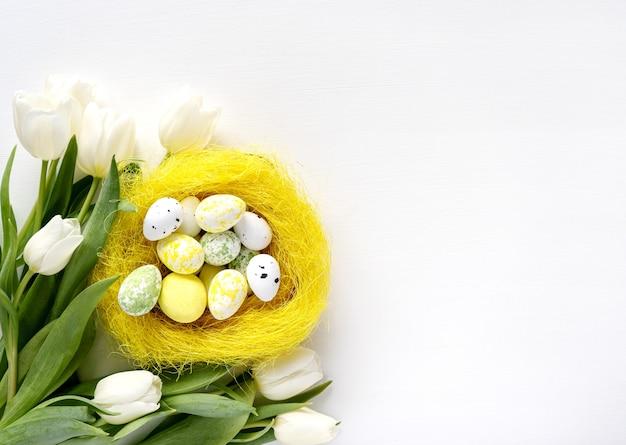 Цветное пасхальное яйцо и белый букет цветов тюльпанов на белом столе