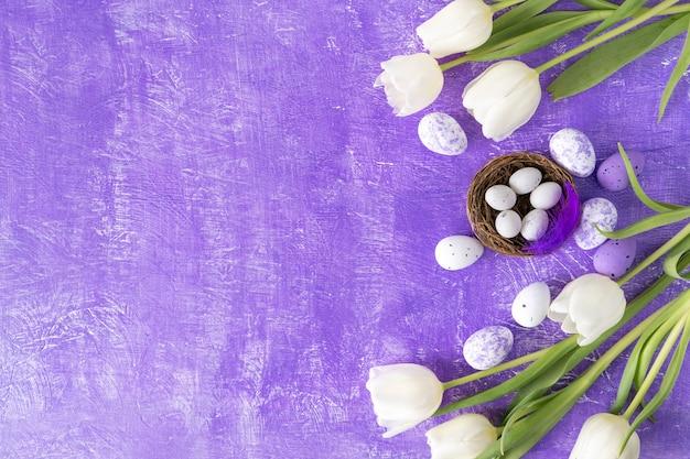 Раскрасьте пасхальные яйца и белые тюльпаны на фиолетовом фоне с копией пространства.