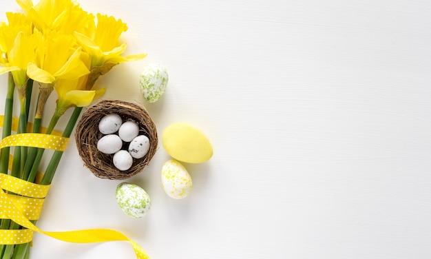 Цветное пасхальное яйцо и букет желтых цветов на белом фоне, копия пространства, вид сверху, поздравительная открытка. пасхальный фон