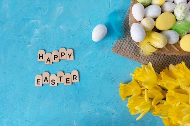 Цветное пасхальное яйцо и желтые цветы на синем фоне с текстом.