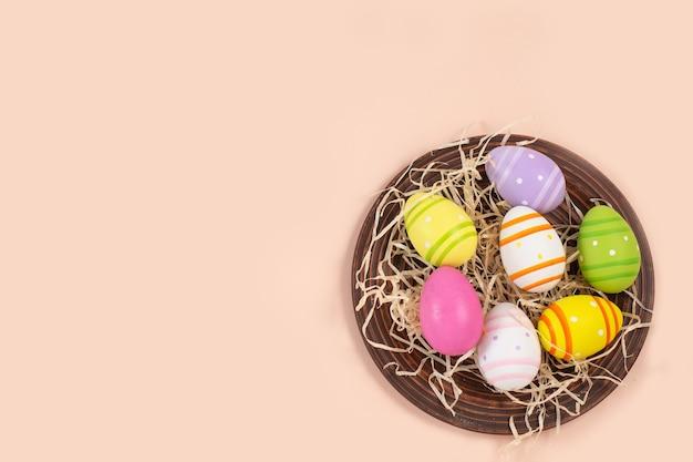 Цветные яйца в деревенской тарелке с соломой на бежевом пастельном столе