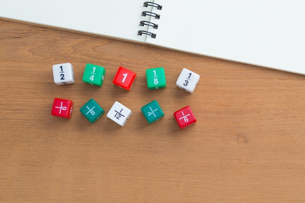 Color fraction dices, blank white notebook on wooden desk