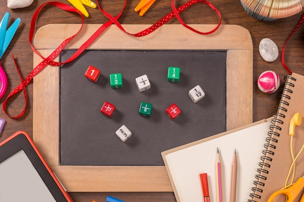Color fraction dices on small blackboard with school supplies on wooden table