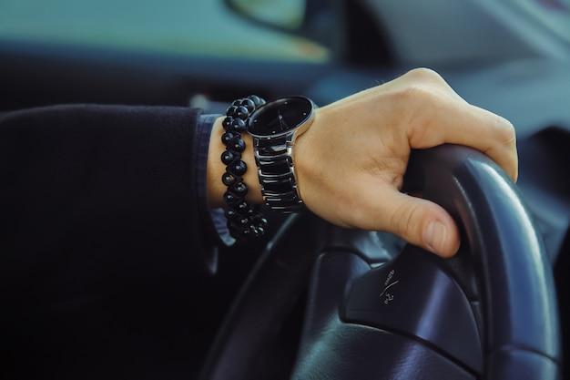 자동차에 시계와 팔찌가 있는 성인 남성 손의 컬러 이미지 사진을 닫습니다