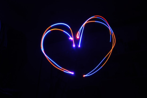 Color light lamp move heart shape on long exposure shot in the dark.