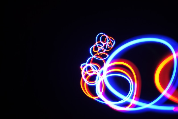 Color light lamp move twist cycles on long exposure shot in the dark. Premium Photo