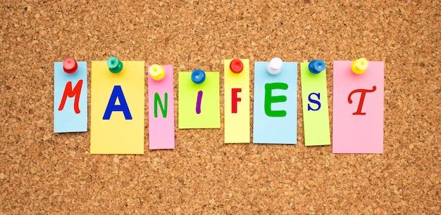 Цветные заметки с буквами, прикрепленными к доске. слово манифест. рабочая среда.