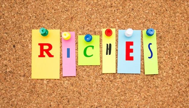 Цветные заметки с буквами, прикрепленными к доске. слово богатство.