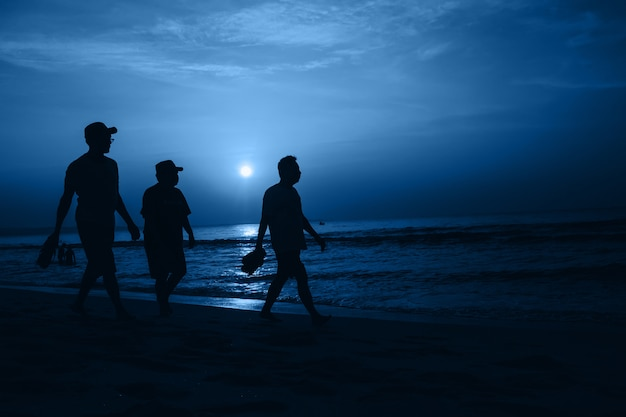 2020 년 클래식 블루의 색상. 해변을 걷는 사람들의 실루엣
