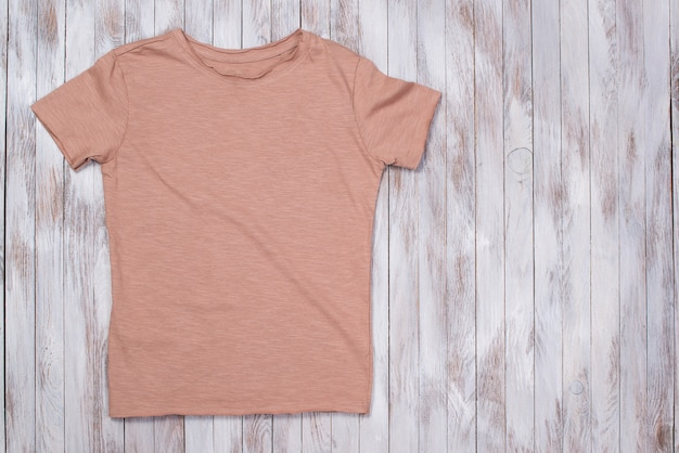 コピースペース付きカラーペイントtシャツ。 tシャツのモックアップ、フラットレイ。スタイリッシュな木製テーブル。
