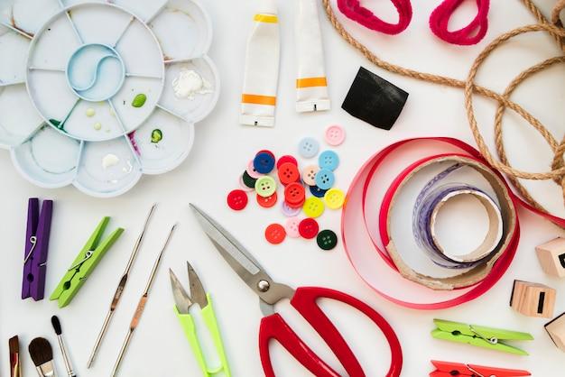 색상 팔레트; 아크릴 페인트 튜브; 크로 셰 뜨개질 바늘; 버튼; 리본; 가위; 옷 핀과 문자열 흰색 배경에 고립