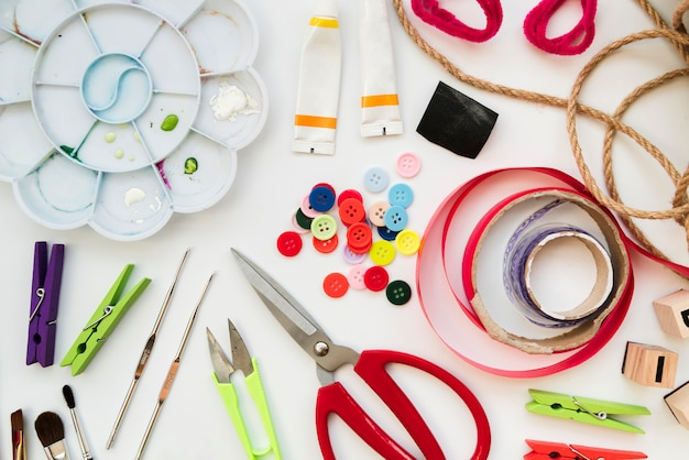 Color palette; acrylic paint tube; crochet needles; buttons; ribbon; scissor; clothespin and string isolated on white background