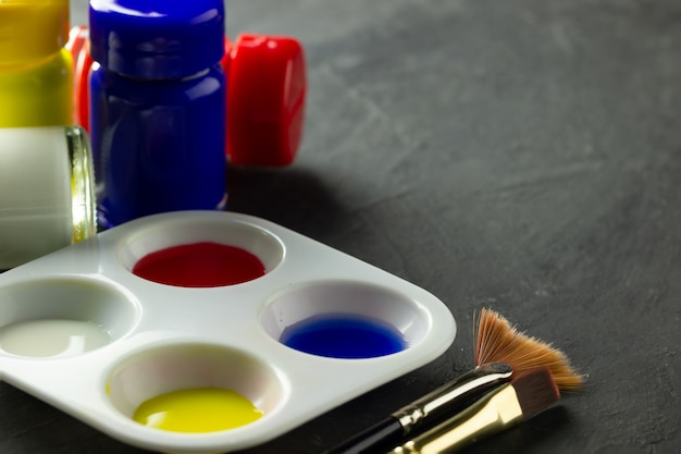 Color palette and artist paint brush with poster color bottle on black cement floor