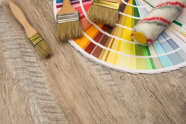 Руководство по цветовой палитре и валик с кистью на деревянной доске