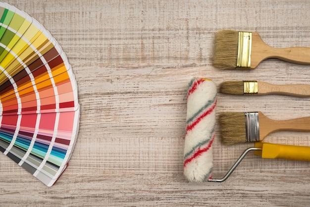 木の板のカラーパレットガイドとペイントブラシローラー