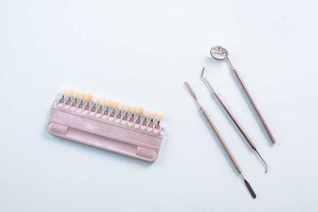 Цветовая палитра различных оттенков зубов и стоматологических инструментов на синем фоне. концепция отбеливания зубов