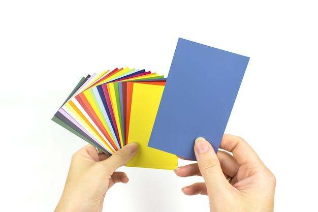 白い背景の手にカラーパレットのサンプル。レインボーサンプルカラーカタログ。