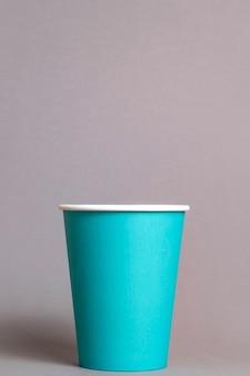 Цветной бумажный стаканчик на сером фоне. место для текста