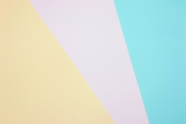 Color papers geometry flat composition background with yellow, pink and blue pastel tones