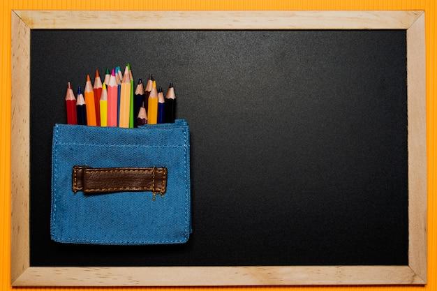 オレンジの背景に黒板にミニバッグの中の色ペン。