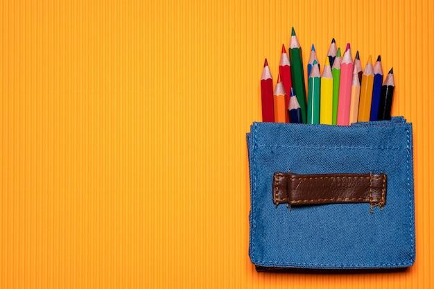 オレンジの背景にミニバッグのカラーペン。