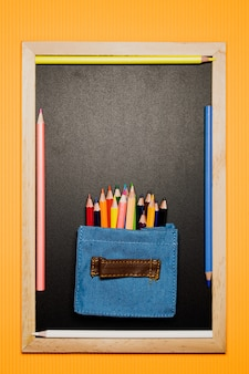 Color pen in mini bag on blackboard on orange background.