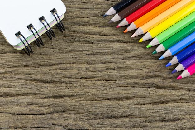 色鉛筆と木目調の背景にメモ帳