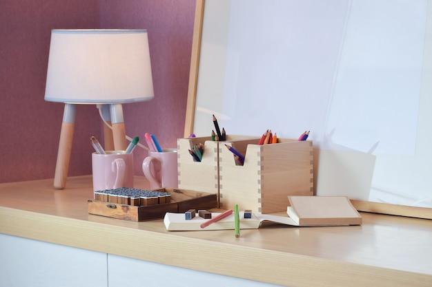 아이들을위한 나무 테이블에 노트북으로 설정 컬러 연필 및 도장
