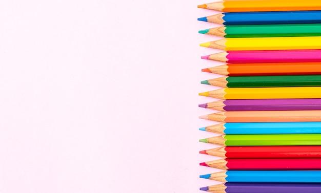 Цветной карандаш на розовом фоне с копией пространства