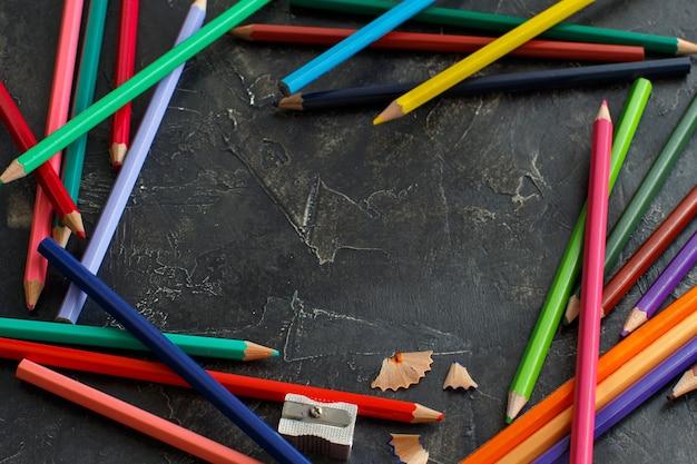 Цветные карандаши и точилка на темном столе