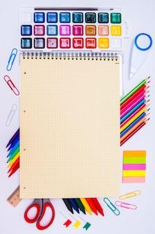 Цветные карандаши и акварели с желтой записной книжкой на белом, снова в школу, канцелярские товары
