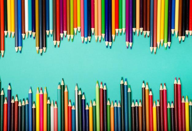 青い背景上の波に配置された色鉛筆