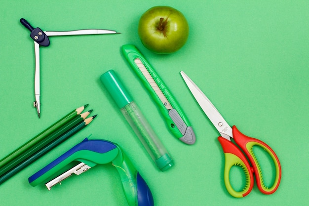 Цветные карандаши, компас, степлер, фломастер, нож для бумаги, яблоко и ножницы на зеленом фоне. вид сверху. снова в школу концепции. школьные принадлежности